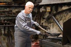 资深铁匠在forgingin铁匠铺前加热项目 免版税库存图片