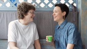资深食用母亲和年轻的女儿谈话在沙发,一起微笑和咖啡 愉快的系列 股票视频