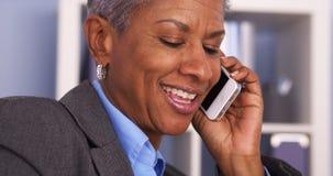 资深黑人女实业家微笑和谈话在智能手机 库存照片