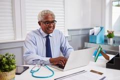 资深黑人男性医生在使用膝上型计算机的工作在办公室 免版税库存照片