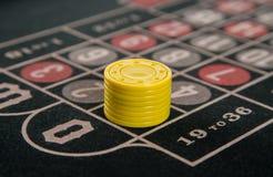 赌博在与黄色芯片的轮盘赌桌上 库存照片