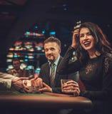 赌博在赌博娱乐场的上层阶级夫妇 免版税库存照片