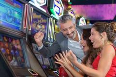 赌博在赌博娱乐场的人们演奏老虎机 库存图片
