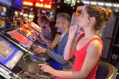 赌博在赌博娱乐场的年轻小组人民 图库摄影