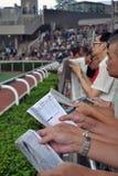 赌博在赛马的人们 免版税库存照片