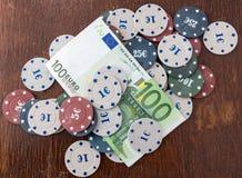 赌博娱乐场芯片和卡片和一一百欧元在桌上 免版税库存图片