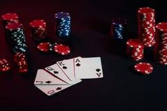 赌博娱乐场芯片和卡片在黑桌上浮出水面 赌博,时运、比赛和娱乐概念-接近  免版税库存照片