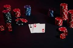 赌博娱乐场芯片和卡片在黑桌上浮出水面 赌博,时运、比赛和娱乐概念-接近  免版税库存图片