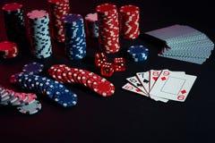 赌博娱乐场芯片和卡片在黑桌上浮出水面 赌博,时运、比赛和娱乐概念-接近  免版税图库摄影