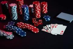 赌博娱乐场芯片和卡片在黑桌上浮出水面 赌博,时运、比赛和娱乐概念-接近  库存照片