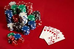赌博娱乐场赌博的啤牌设备和娱乐概念-接近纸牌和芯片在红色背景 皇家 库存照片
