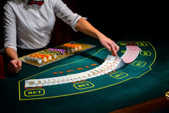 赌博娱乐场:经销商拖曳啤牌卡片 库存图片