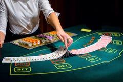 赌博娱乐场:经销商拖曳啤牌卡片 免版税图库摄影