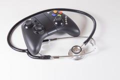 黑赌博控制器和医生听诊器 免版税库存图片