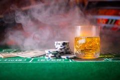 赌博,时运、比赛和娱乐概念-关闭赌博娱乐场芯片和威士忌酒玻璃在桌上 免版税库存照片