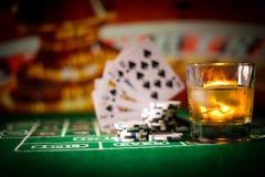 赌博,时运、比赛和娱乐概念-接近赌博娱乐场芯片和威士忌酒玻璃在桌上 库存照片
