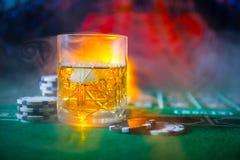 赌博,时运、比赛和娱乐概念-接近赌博娱乐场芯片和威士忌酒玻璃在桌上 库存图片