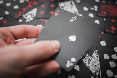 赌博 两一点在手中02张黑色的纸牌背景 图库摄影
