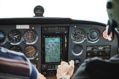 赛斯纳有两名飞行员的skyhawk 172飞机驾驶舱的特写镜头  免版税库存图片
