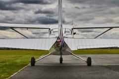 赛斯纳172 Skyhawk 2飞机对称背面图在一条跑道的有剧烈的天空背景 库存图片