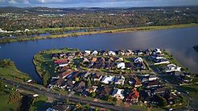 赛船会在湖的Coomera河旁边浇灌Parkland英属黄金海岸草玩耍区域议院庄园, 免版税图库摄影