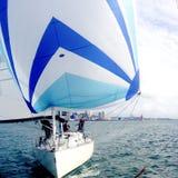 赛跑与一艘蓝色大三角帆的游艇 图库摄影
