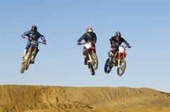 赛跑与天空的摩托车越野赛男性竟赛者 免版税库存照片