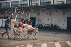 赛跑与购物台车的不同种族的青年人 图库摄影