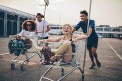 赛跑与购物台车的青年人 免版税库存图片
