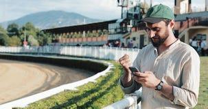 赛跑俄国的高加索竞技场马北pyatigorsk 人在与智能手机的一匹马打赌了 年轻人使用在跑马场的一个智能手机 编辑胜利 股票视频