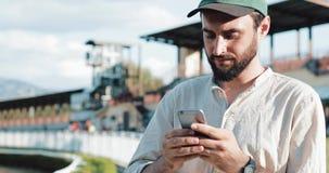 赛跑俄国的高加索竞技场马北pyatigorsk 人在与智能手机的一匹马打赌了 年轻人使用在跑马场的一个智能手机 编辑胜利 股票录像
