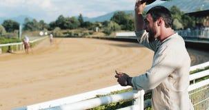 赛跑俄国的高加索竞技场马北pyatigorsk 观众的热心者赛马的 在马打赌的人 与智能手机的编辑胜利 影视素材