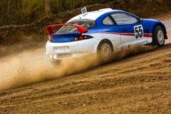 赛跑在一条多灰尘的路的速度汽车 免版税库存照片