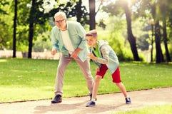 赛跑在夏天公园的祖父和孙子 免版税库存图片