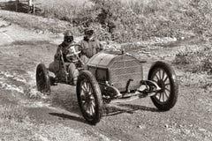 赛跑在老土路的古董车 免版税库存图片