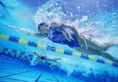 赛跑在水池的女性专业参加者 库存图片