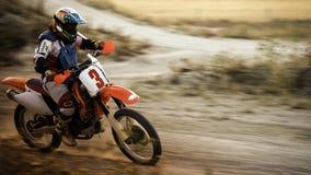 赛跑沿泥铺跑道的Enduro自行车 库存图片
