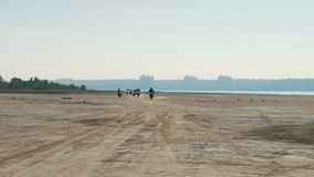 赛跑沿从很远的沙滩的许多摩托车骑士 骑自行车的人专栏 股票视频