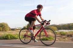 赛跑的成套装备专业男性骑自行车者在自行车的乘驾期间户外 免版税图库摄影