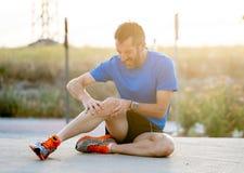 赛跑者在痛苦中的拿着他的膝盖在拉伤肌肉以后 免版税图库摄影