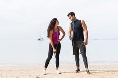 赛跑者夫妇有休息在训练在海滩男人和妇女站立适合的男性和女性健身的体育赛跑者以后 库存图片
