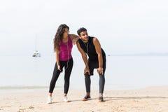 赛跑者夫妇有休息在训练在海滩男人和妇女站立适合的男性和女性健身的体育赛跑者以后 免版税库存图片