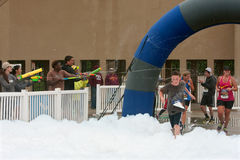 赛跑者奔跑通过喷枪和泡沫在5K种族 库存照片