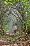 赛跑者妇女横越全国的赛跑在森林里 免版税库存照片