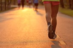 赛跑者的脚在晚上光的 免版税库存图片