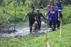 赛跑者设法征服一条泥泞的轨道 免版税库存图片