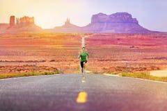赛跑者跑在路纪念碑谷的人运动员 免版税图库摄影