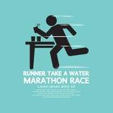 赛跑者采取在马拉松长跑标志的水 库存图片