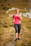赛跑者-妇女治理一条道路的阴级射线示波器国家在早期的秋天 免版税库存照片