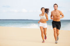 赛跑者-跑在海滩的年轻夫妇 库存照片